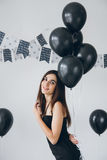 Girl in a black dress with black balloons