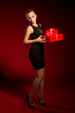 Girl in a black dress with gifts in hands Royalty Free Stock Photography