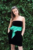 Girl in the black dress with green bow Royalty Free Stock Image