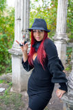 Girl in black. Dress and hat with a gun on vintage background of stone columns Royalty Free Stock Image