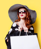 Girl in black dress and hat with shopping bags Royalty Free Stock Photos