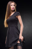 Girl in a black dress holding a gun Royalty Free Stock Image