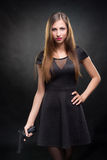 Girl in a black dress holding a gun Royalty Free Stock Photography