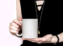 Girl in black dress is holding white cup in hands. Royalty Free Stock Images