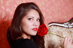 Girl in black dress holds red rose Royalty Free Stock Photography