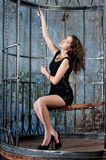 Girl in black dress in metallic cage, inside Royalty Free Stock Photography