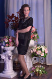 Girl in a black dress next to a vase with flowers Royalty Free Stock Photography