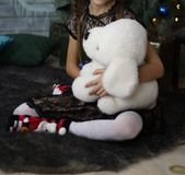 Girl in a black dress is holding a gift, holds a white toy dog. open birthday gifts. Girl in a black dress, with pigtails, holding a gift, holds a white toy dog stock photos