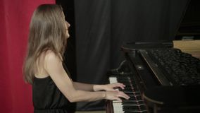 Girl in black dress playing on the piano stock footage
