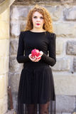 The girl in a black dress with red apple. The girl in a black dress with a red apple Royalty Free Stock Photo