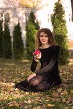 The girl in a black dress with red apple. The girl in a black dress with a red apple Royalty Free Stock Image