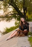 Girl in a black dress with a red dog in the park near the water stock photography