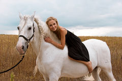 Girl in the black dress is riding on horse Royalty Free Stock Images