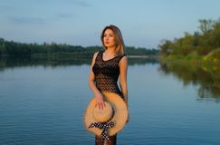 Girl in a black dress by the river in the last rays of the sun stock photos