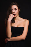 Girl in black dress seductively looking at the camera. Girl standing in a black dress on a black background seductively looking at the camera Stock Photography
