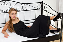 Girl in black dress shoes lying on the bed. Girl in black dress shoes with high heels lying on the bed in the studio shooting Royalty Free Stock Image