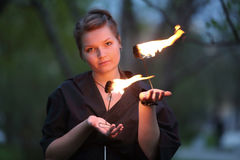 A girl in a black dress shows a fire show. On nature Royalty Free Stock Photos