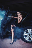 Girl in black dress sits in the car and smoke royalty free stock image
