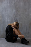 Girl in a black dress, sitting on a background of gray concrete. Wall Stock Photography