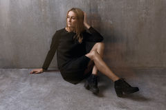 Girl in a black dress, sitting on a background of gray concrete. Wall Stock Image