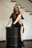 Girl in a black dress sitting on a black barrel-roll under the stairs Royalty Free Stock Image