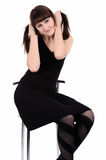 Girl in black dress sitting on a high chair Royalty Free Stock Photo