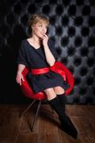 Girl in black dress sitting on a red chair Stock Photos