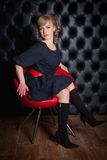 Girl in black dress sitting on a red chair Stock Photo