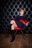 Girl in black dress sitting on a red chair Royalty Free Stock Photography