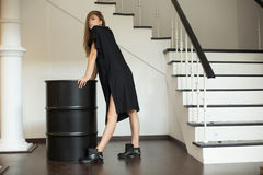 Girl in a black dress standing next to a black barrel-roll stock images