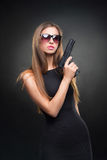 Girl in a black dress and Sunglasses holding a gun Royalty Free Stock Photo