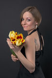 Girl in black dress with tulips Stock Image
