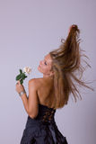 Girl in black dress with turn back holding a white rose Stock Photos