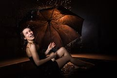 Girl in black dress with umbrella and drops of water royalty free stock image