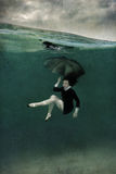 Girl in black dress underwater Stock Photo