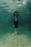 Girl in black dress underwater stock photography