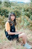 Girl in Black Dungaree and Orange Shirt Sitting of Grass Field royalty free stock photos