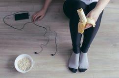 A girl in black elk eating a banana, a phone with headphones, oatmeal. Banana Stock Image
