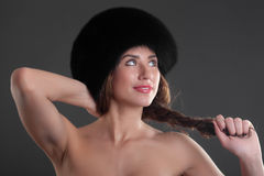 Girl in a black fur cap Royalty Free Stock Photography