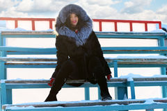 Girl in black fur coat sits on wooden bleachers Royalty Free Stock Images