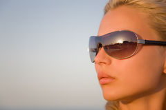 Girl with black glasses isolated on a blue sky Royalty Free Stock Image