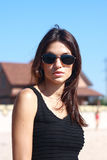 Girl in black gown and sunglasses on beach Royalty Free Stock Image