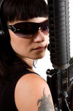 Girl in black with gun. Sexi girl in black dress with gun and headphones Royalty Free Stock Images