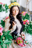 Girl with black hair on the background of flowers Stock Photos
