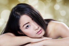 Girl with black hair lying down on her hands Stock Images