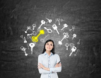Girl with black hair near blackboard with key icon. Dreamy girl with black hair standing near blackboard with key sketches on it. Concept of real estate market Stock Photo