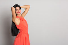 Girl with black hair in orange dress Stock Image