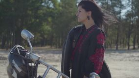 The girl with black hair standing at the motorcycle looking away in front of pine forest. Hobby, traveling and active. The girl with black hair standing at the stock video