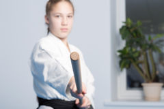 A girl in black hakama standing in fighting pose with wooden jo stick. Selective focus. A girl in black hakama standing in fighting pose with wooden jo stick on stock image