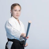 A girl in black hakama standing in fighting pose with wooden jo stick. On white background royalty free stock images